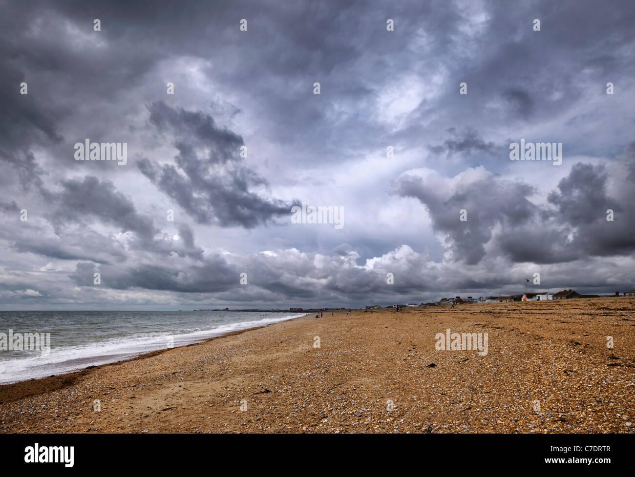 Ciel d'orage sur la plage de galets à Shoreham-by-Sea, Sussex, Angleterre. Photo Stock