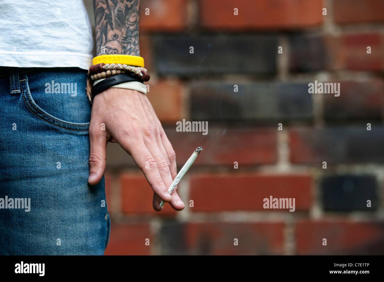 L'adolescent tatoué tenant un joint de cannabis Banque D'Images