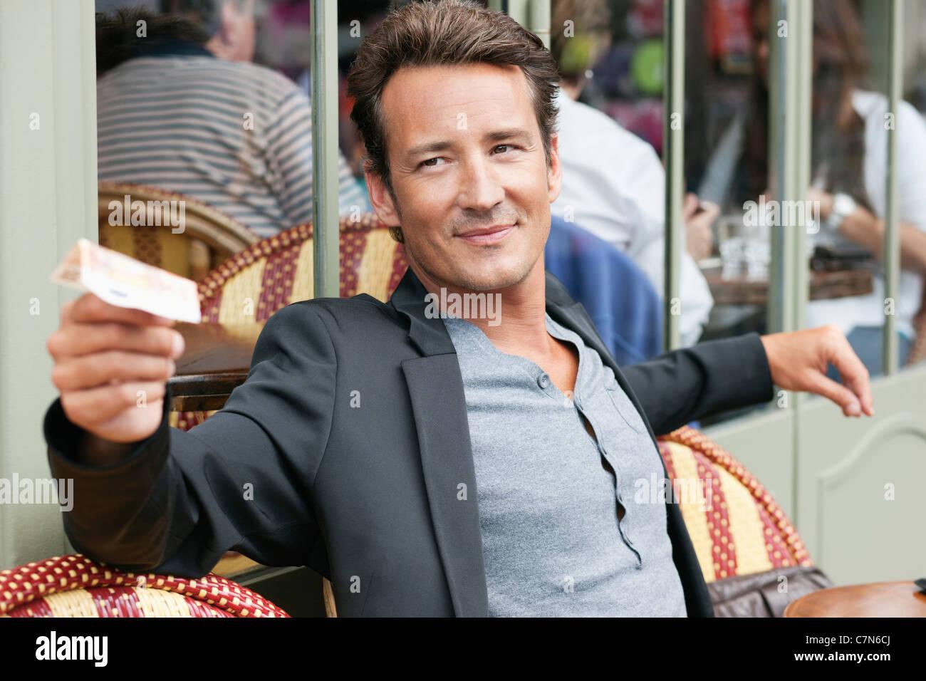 L'homme de loi de payer dans un restaurant, Paris, Ile-de-France, France Photo Stock