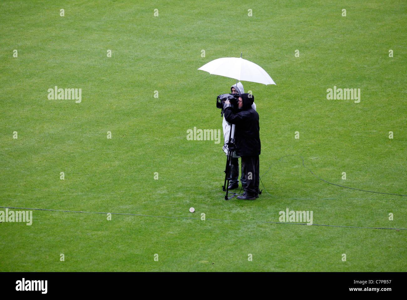 L'équipe de caméras de télévision, lors d'une couverture en direct d'un événement, debout sous la pluie sous un parapluie. L'Allemagne. Banque D'Images