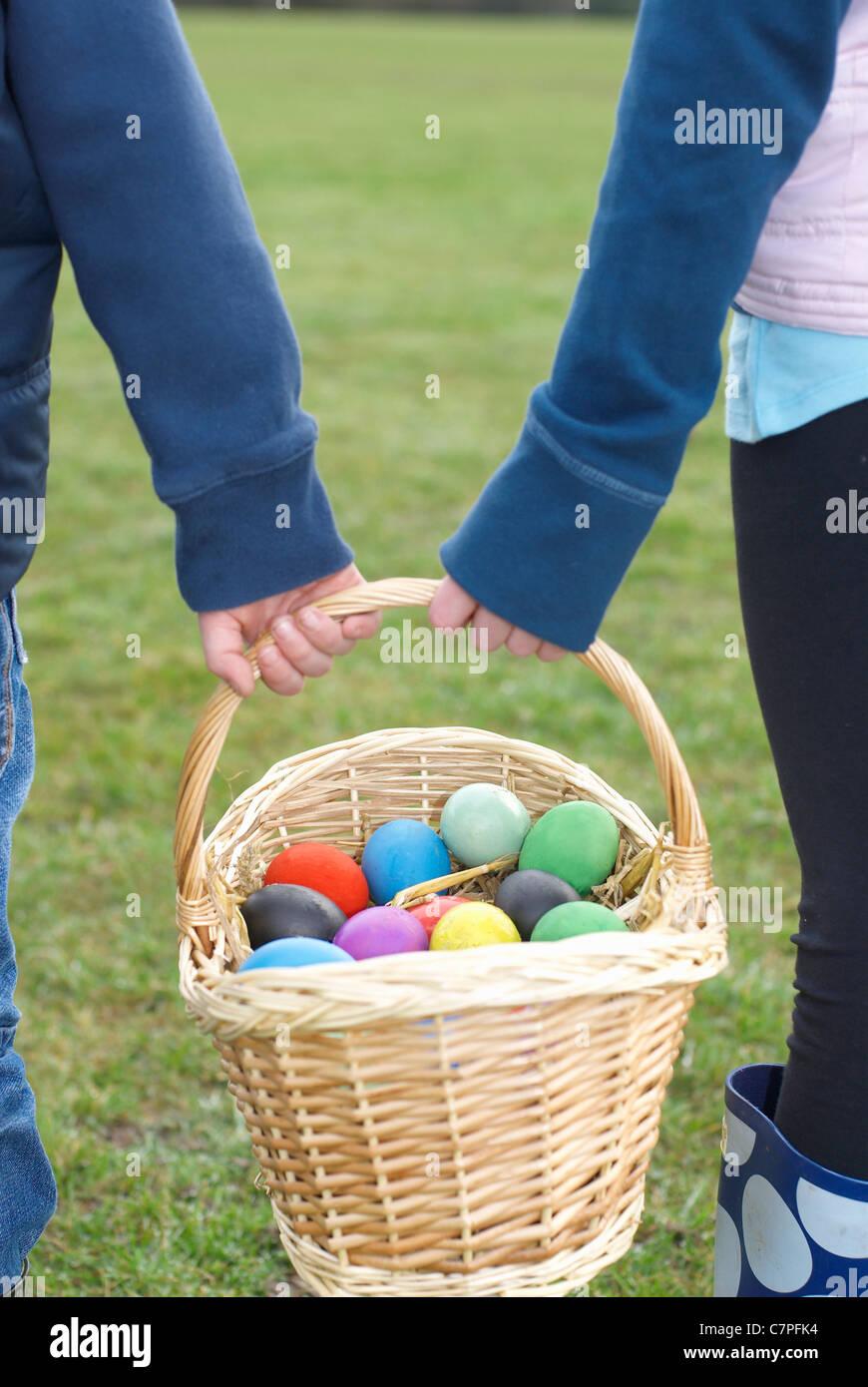 Enfants portant panier d'oeufs de Pâques Photo Stock
