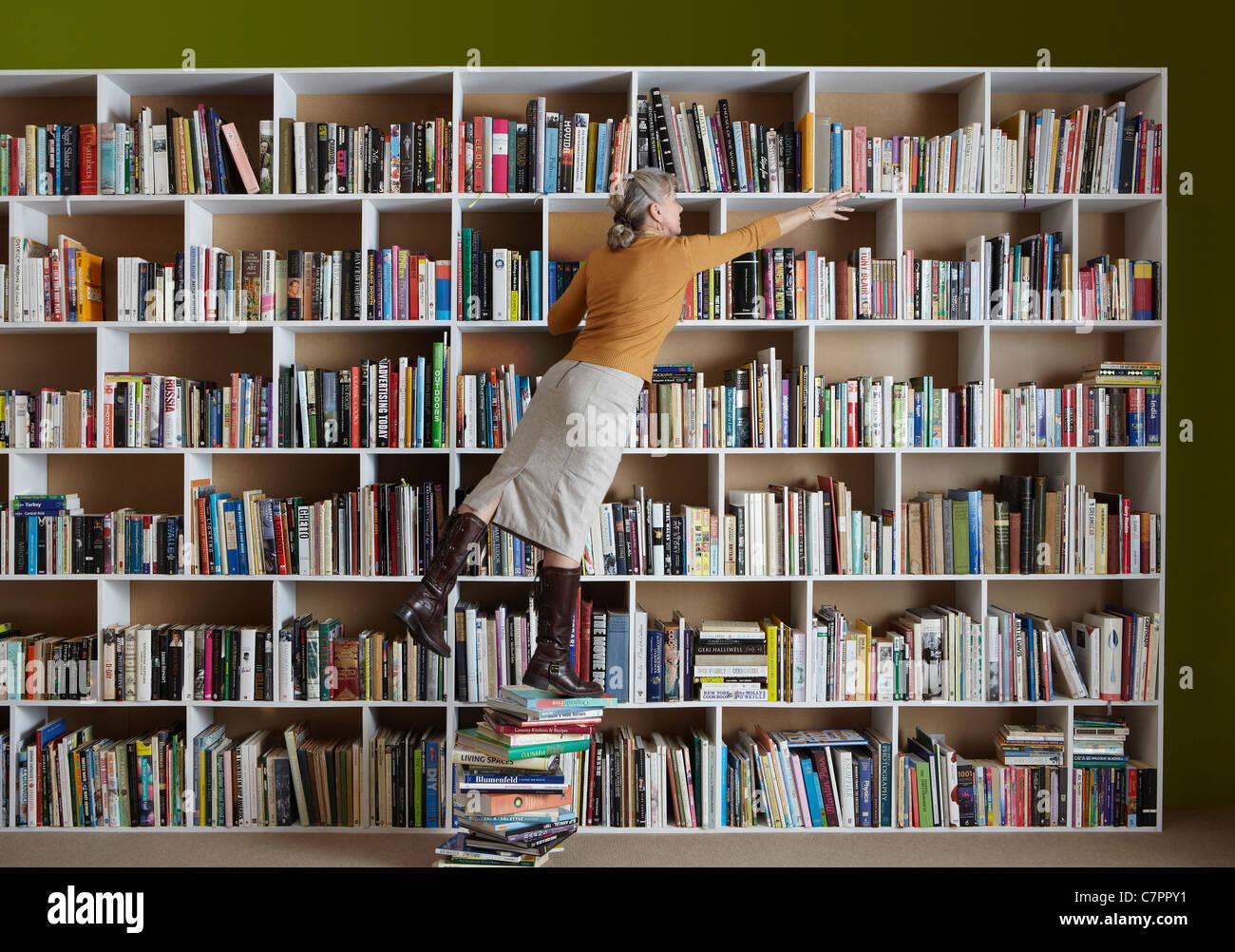 Femme plus âgée debout sur pile de livres Banque D'Images
