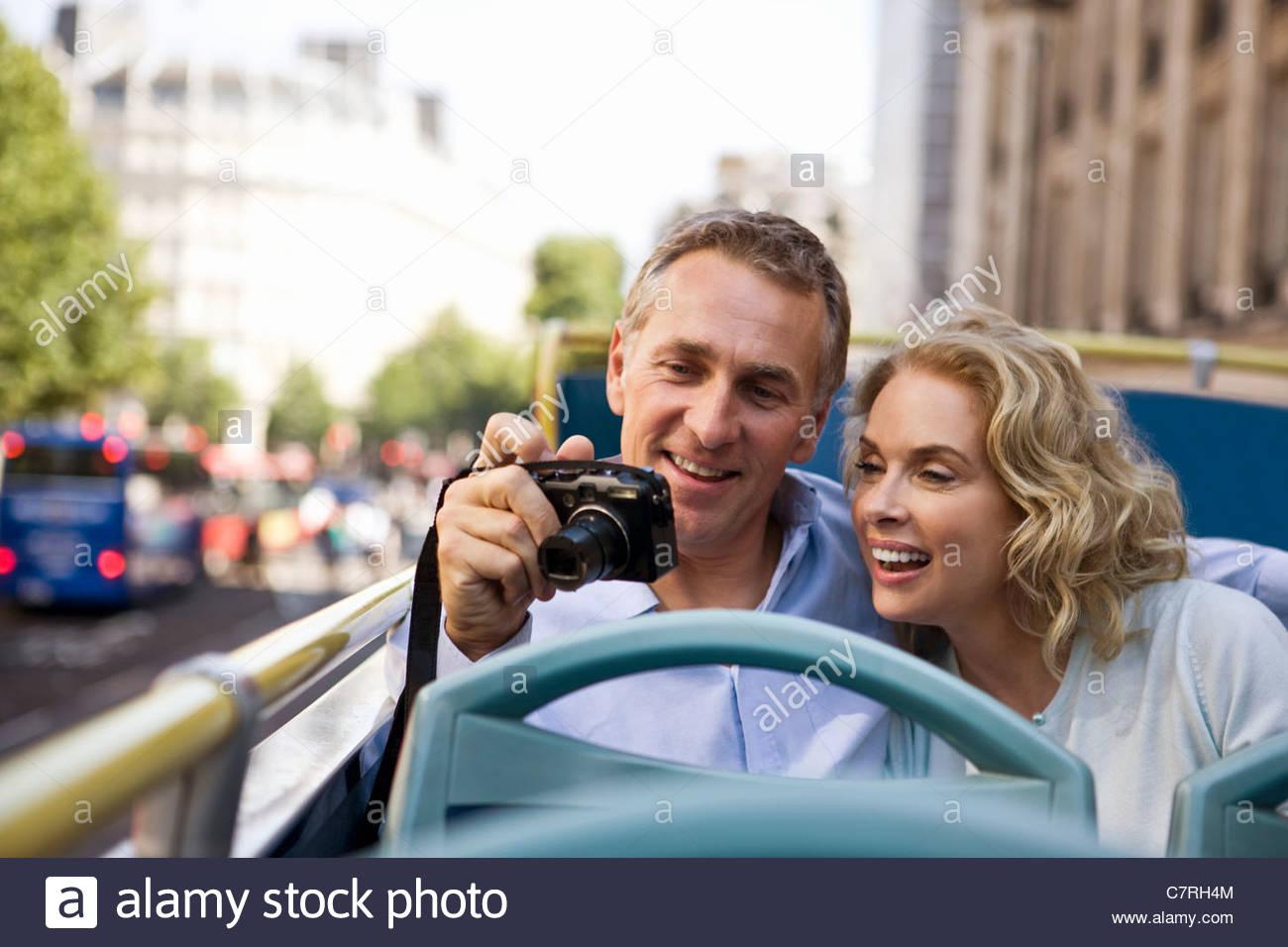 Un couple assis sur un bus de tourisme, holding a camera Photo Stock