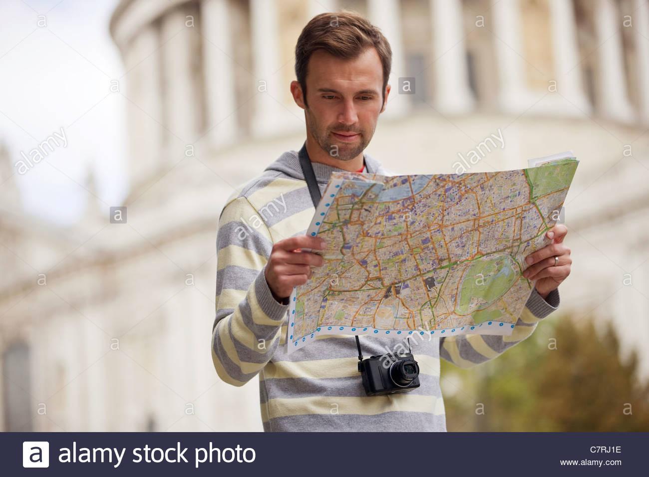 Une mid-adult man standing en face de la cathédrale St Paul, en regardant une carte Photo Stock