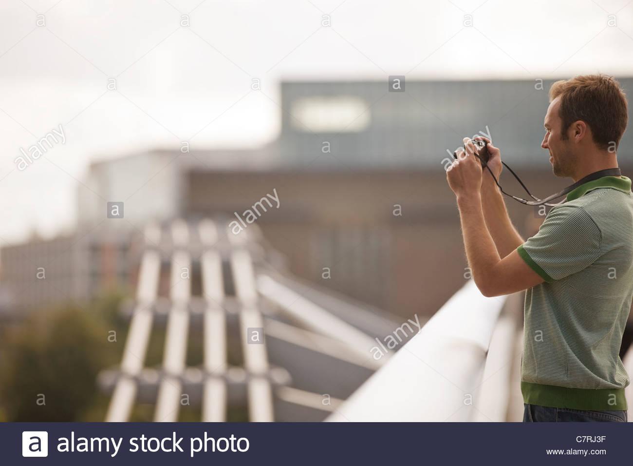 Une mid-adult man standing on the Millennium Bridge, de prendre une photo Photo Stock