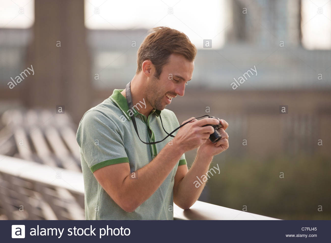 Une mid-adult man looking at photos sur son appareil photo Photo Stock
