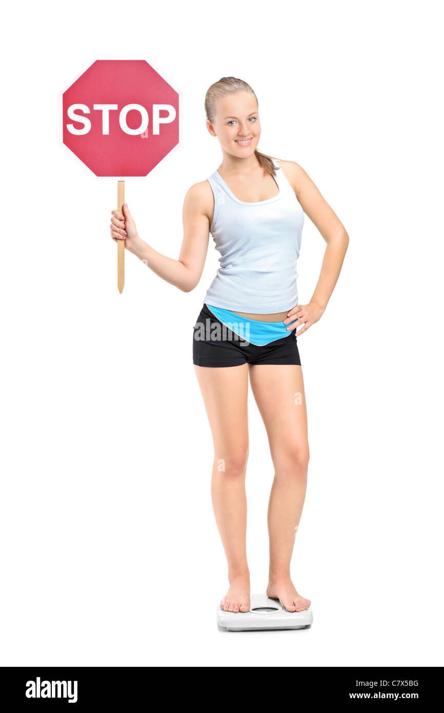 Portrait d'une fille de perte de poids debout sur une échelle de poids et la tenue d'un signe de la Photo Stock