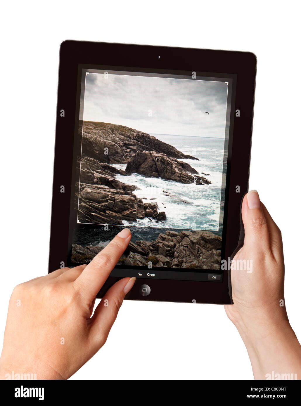 Mains tenant un iPad2 à l'aide d'une app Photoshop pour modifier une photo Photo Stock