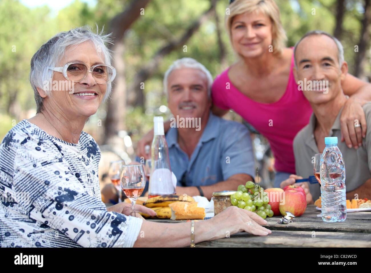 Senior woman having un pique-nique avec des amis Banque D'Images