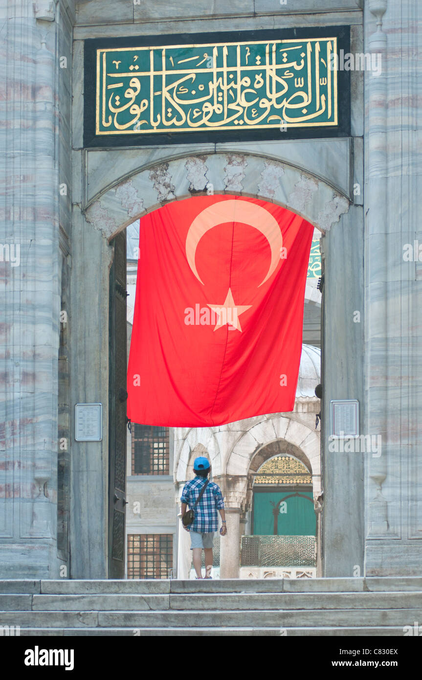 Un visiteur de la mosquée bleue à Istanbul avec un grand drapeau turc accroché au-dessus. Photo Stock