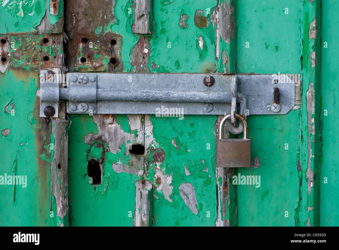 Vieille porte en bois vert avec le gros boulon et d'un cadenas. Photo Stock