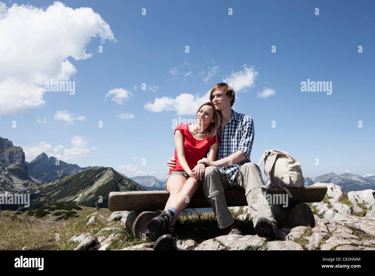 Couple assis sur un banc sur la colline Photo Stock