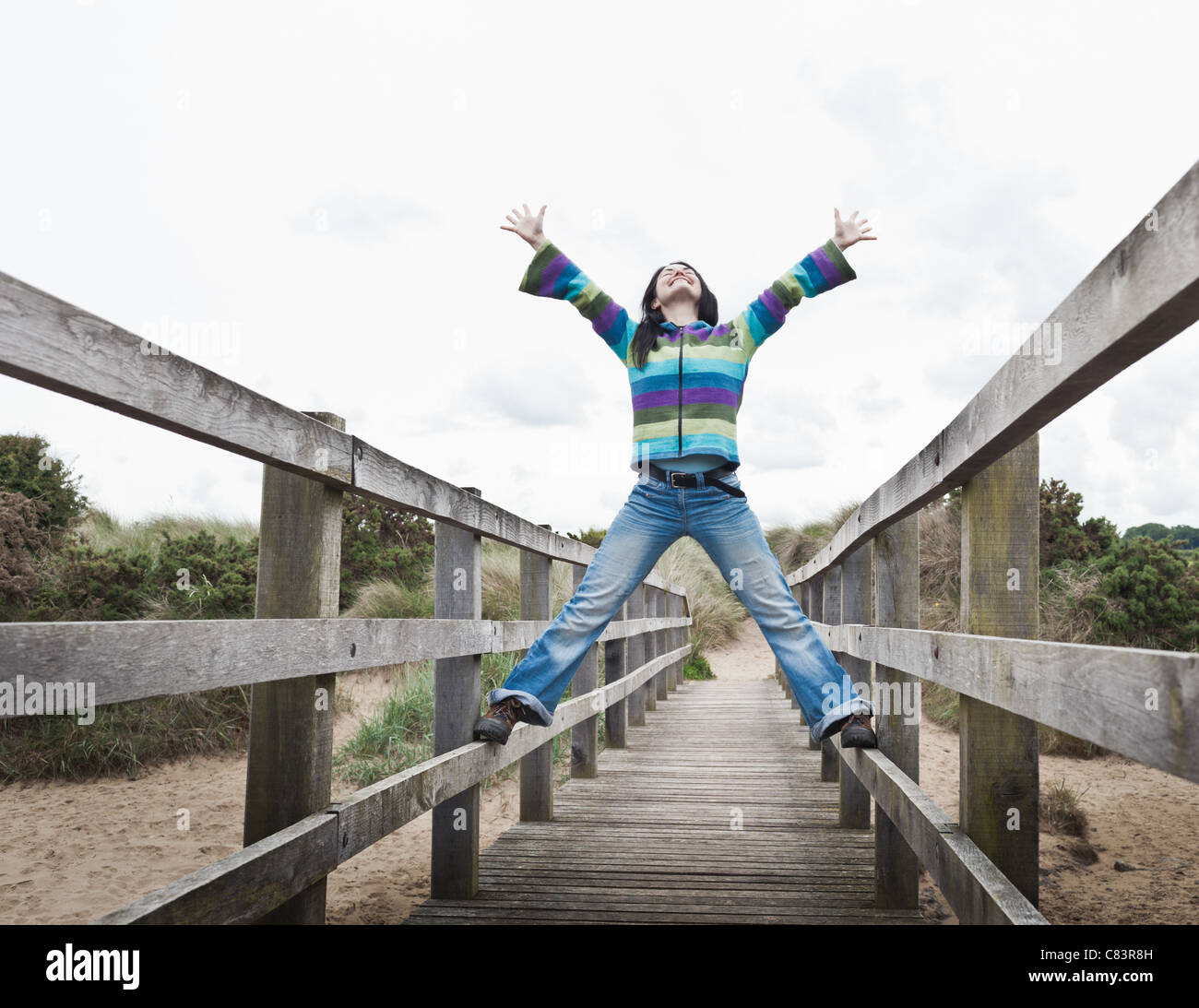 Girl playing on pier on beach Photo Stock