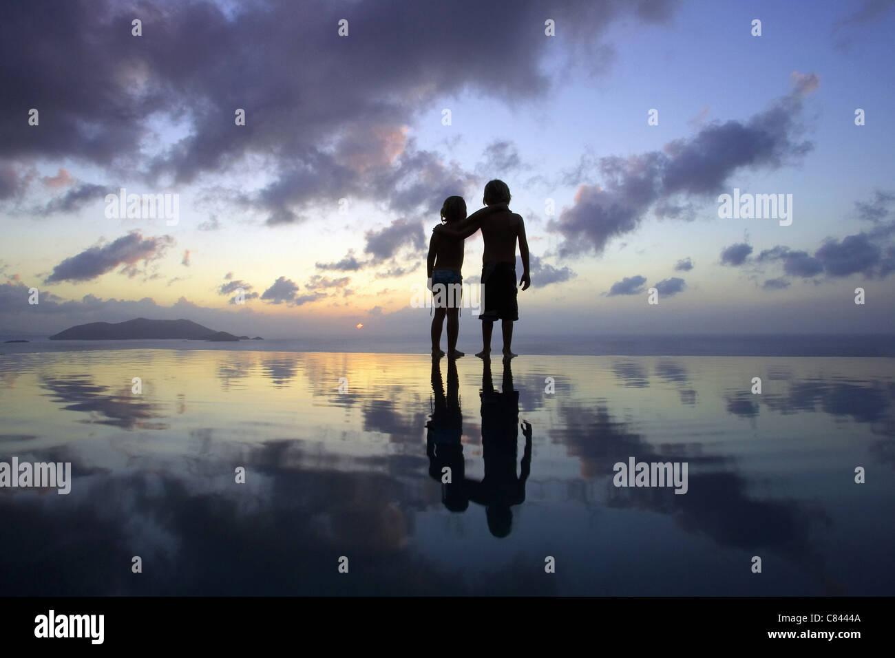 Enfants se tenant sur la plage au coucher du soleil Photo Stock