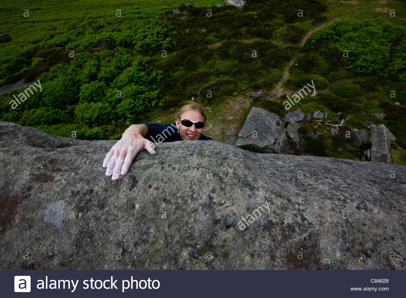 Man climbing steep rock face Photo Stock