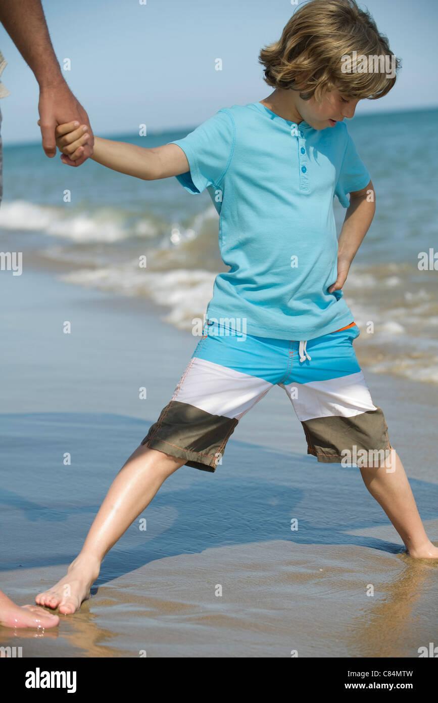 Garçon debout avec les jambes écartées dans le sable humide à la plage Photo Stock