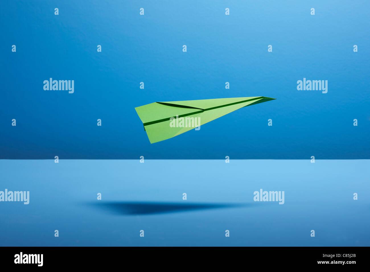 Avion en papier contre l'arrière-plan gris Photo Stock