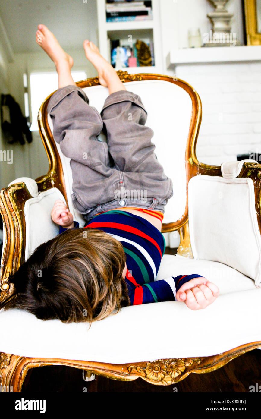 Petit garçon assis à l'envers sur une chaise Photo Stock