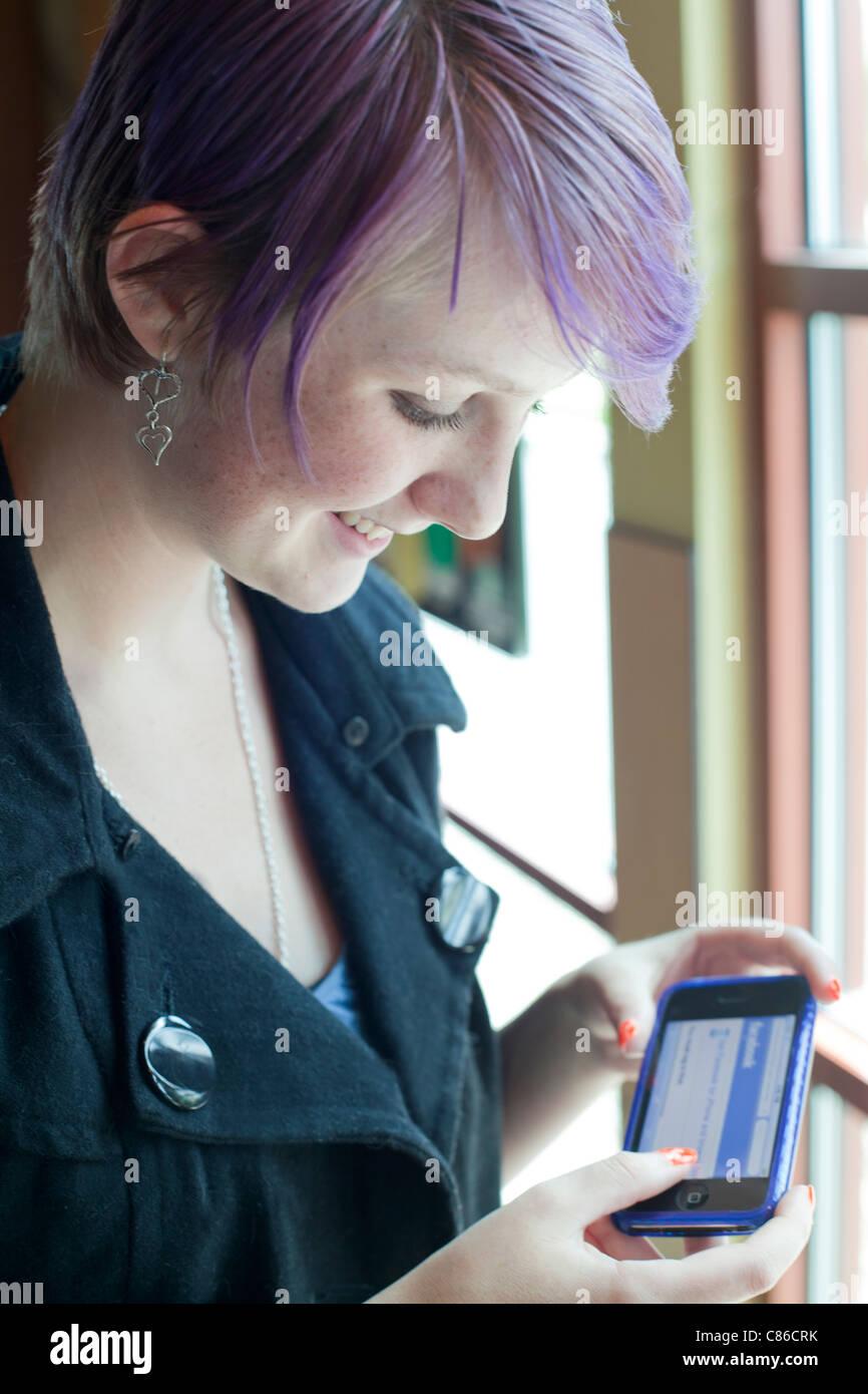 Fille de l'adolescence à l'aide de smart phone d'utiliser facebook Photo Stock