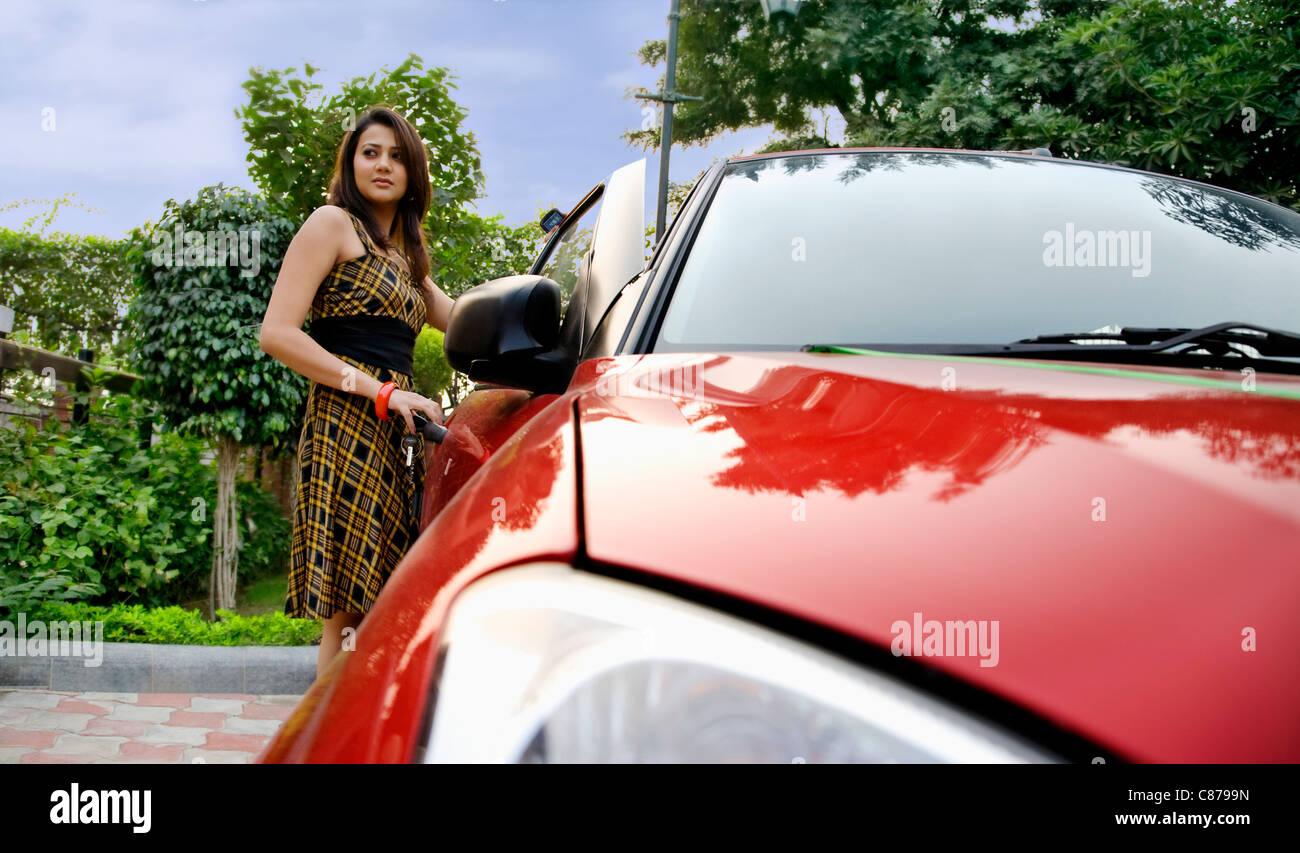 Femme debout à côté d'une voiture Banque D'Images