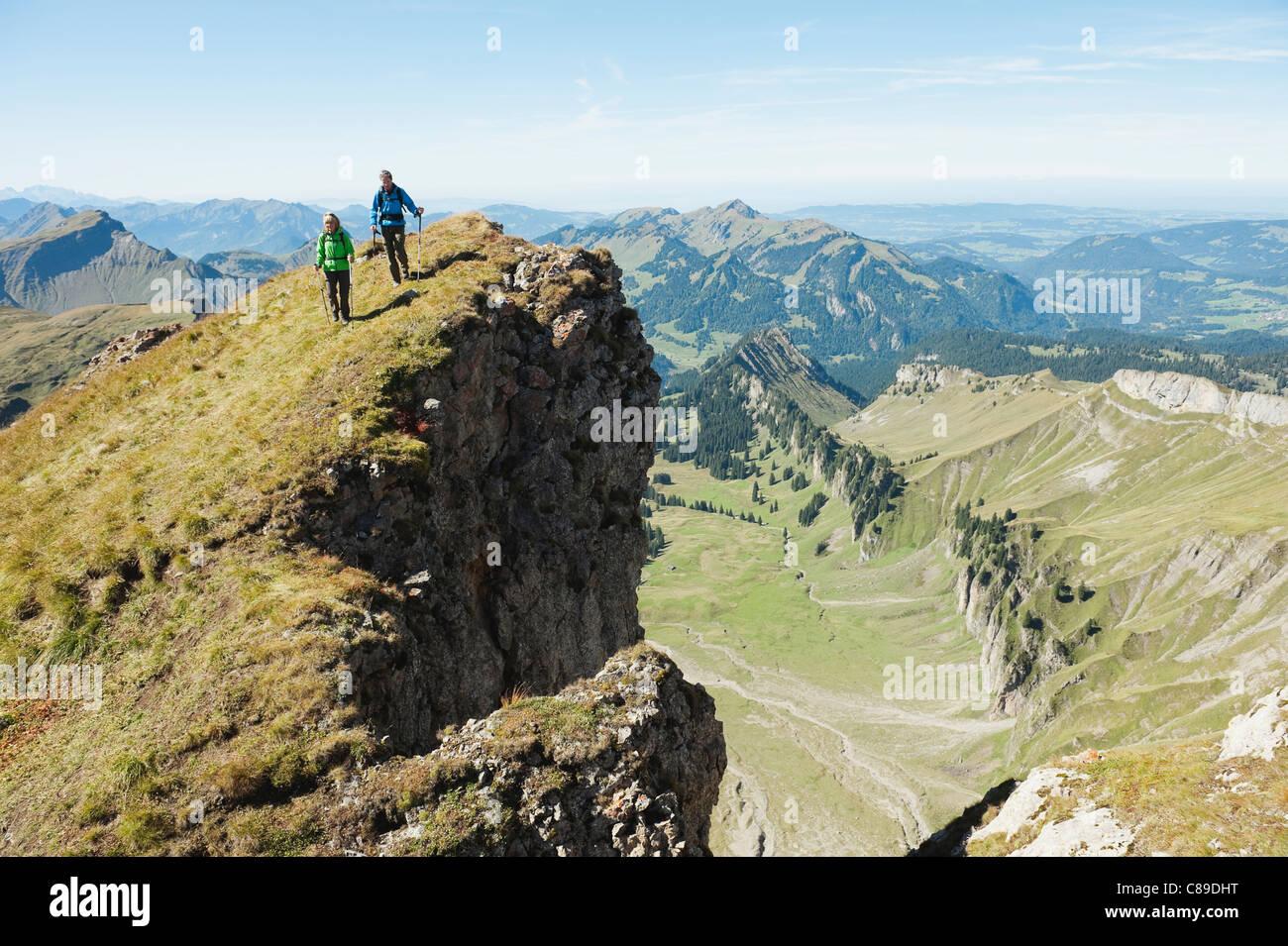 L'Autriche, Kleinwalsertal, l'homme et la femme en randonnée sur les bord de la falaise Photo Stock