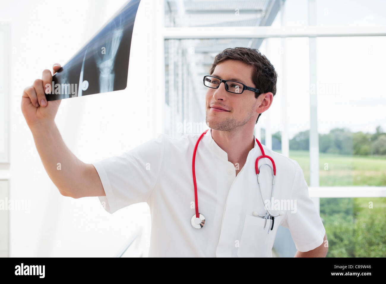 Germany, Bavaria, Diessen am Ammersee, Young doctor examining x-ray, smiling Photo Stock