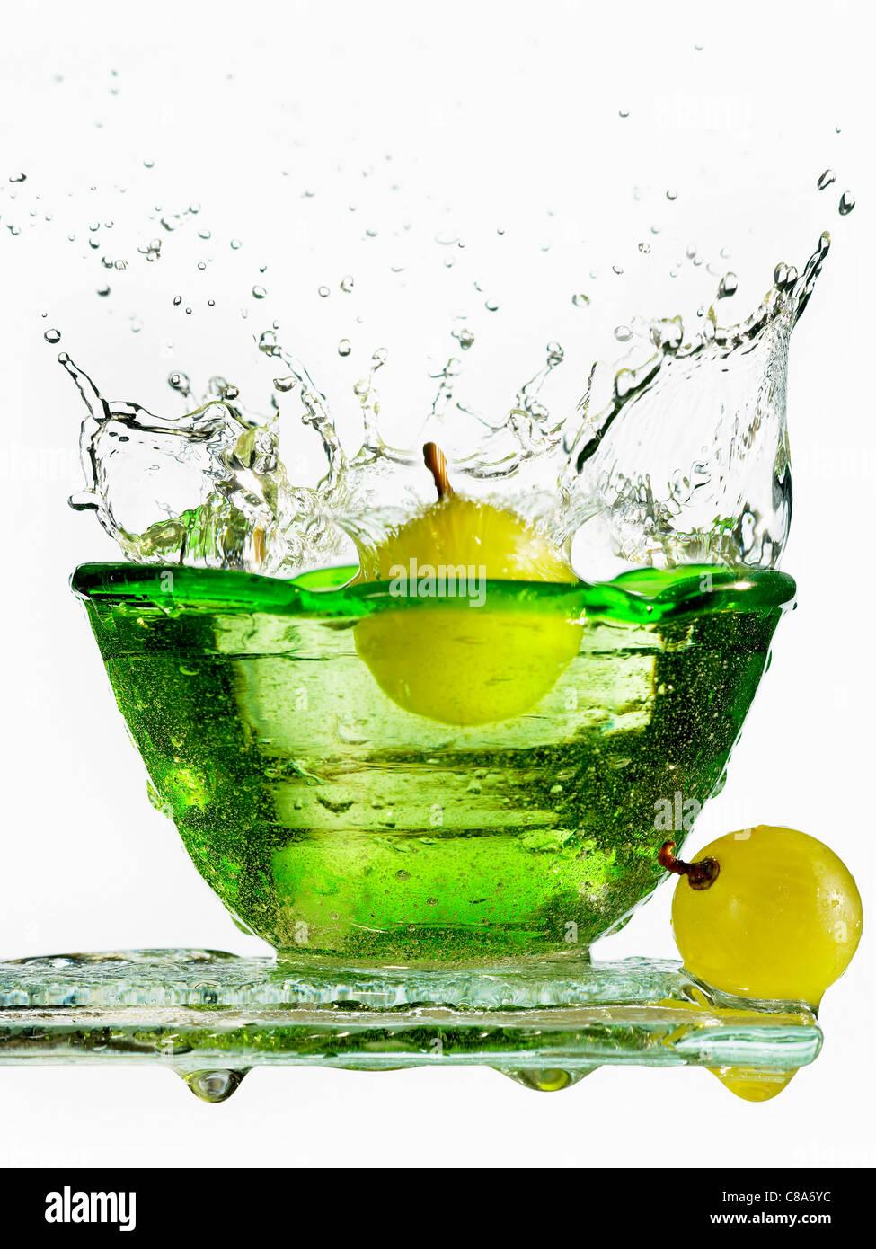 Un raisin de tomber dans un bol d'eau fraîche Photo Stock