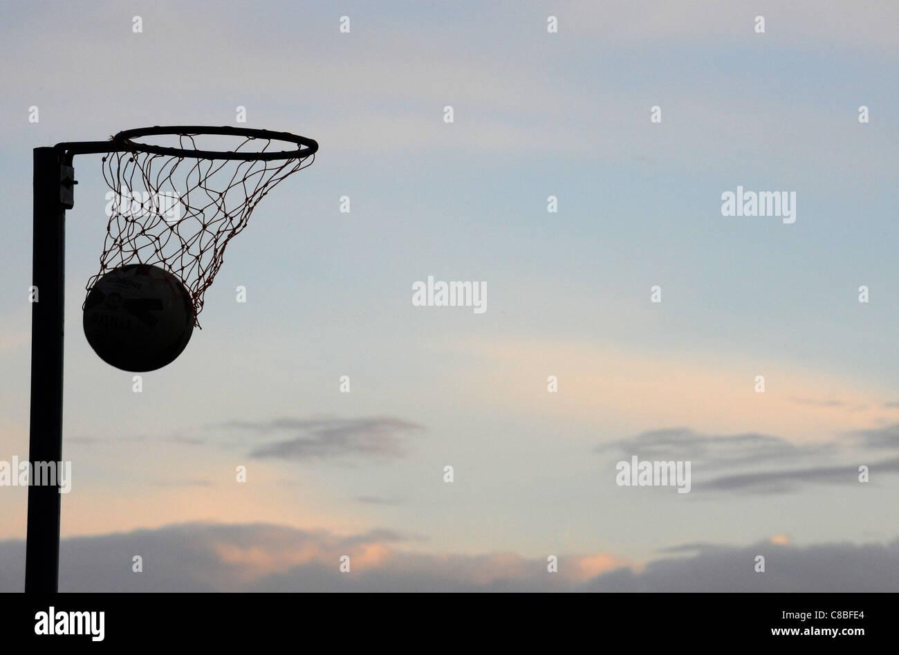 La silhouette d'un passage dans un cerceau de netball avec pas de joueurs au crépuscule. Photo Stock