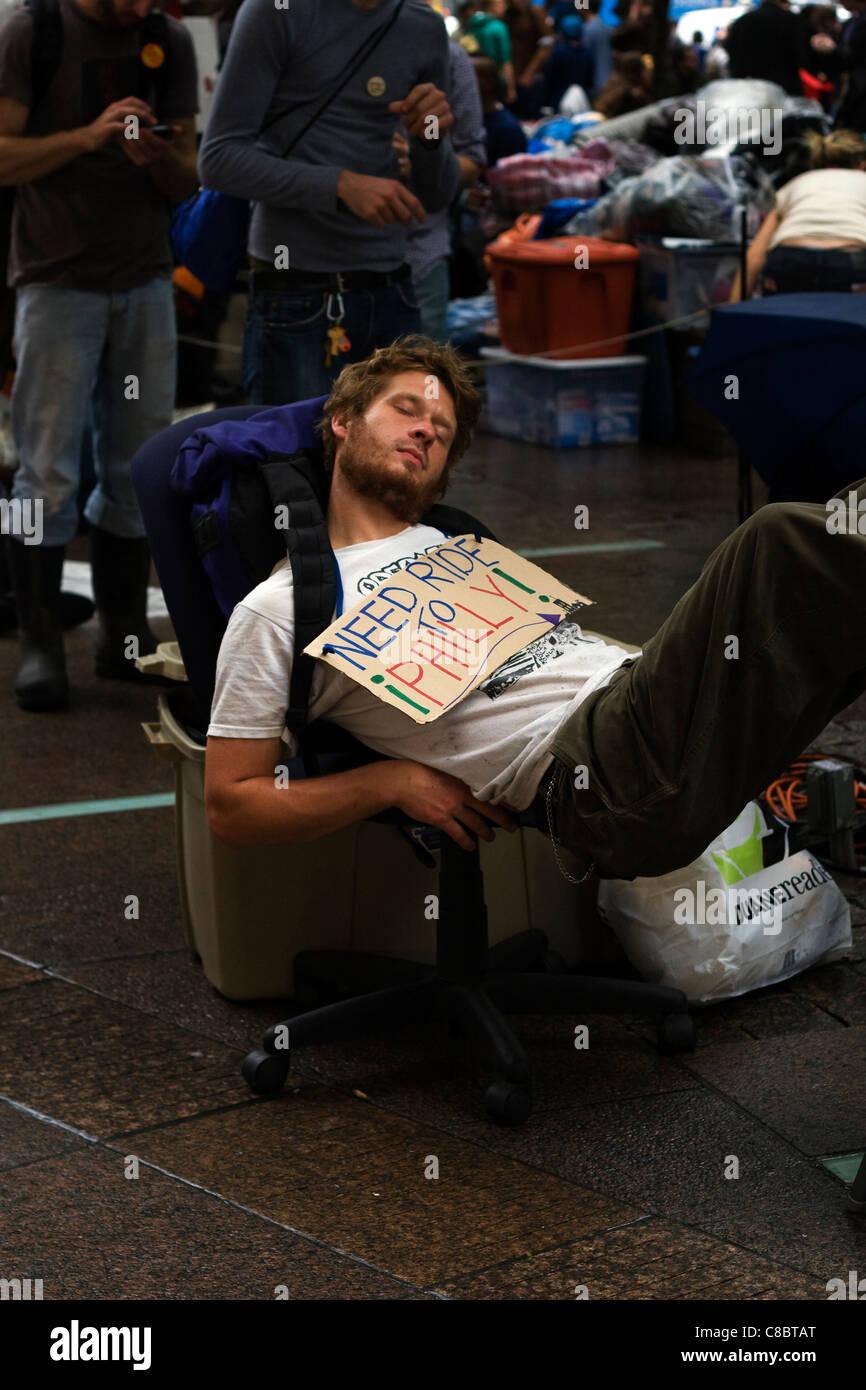 Occupy Wall Street manifestant nommé Luc se reposant dans une chaise de bureau à l'intérieur Photo Stock