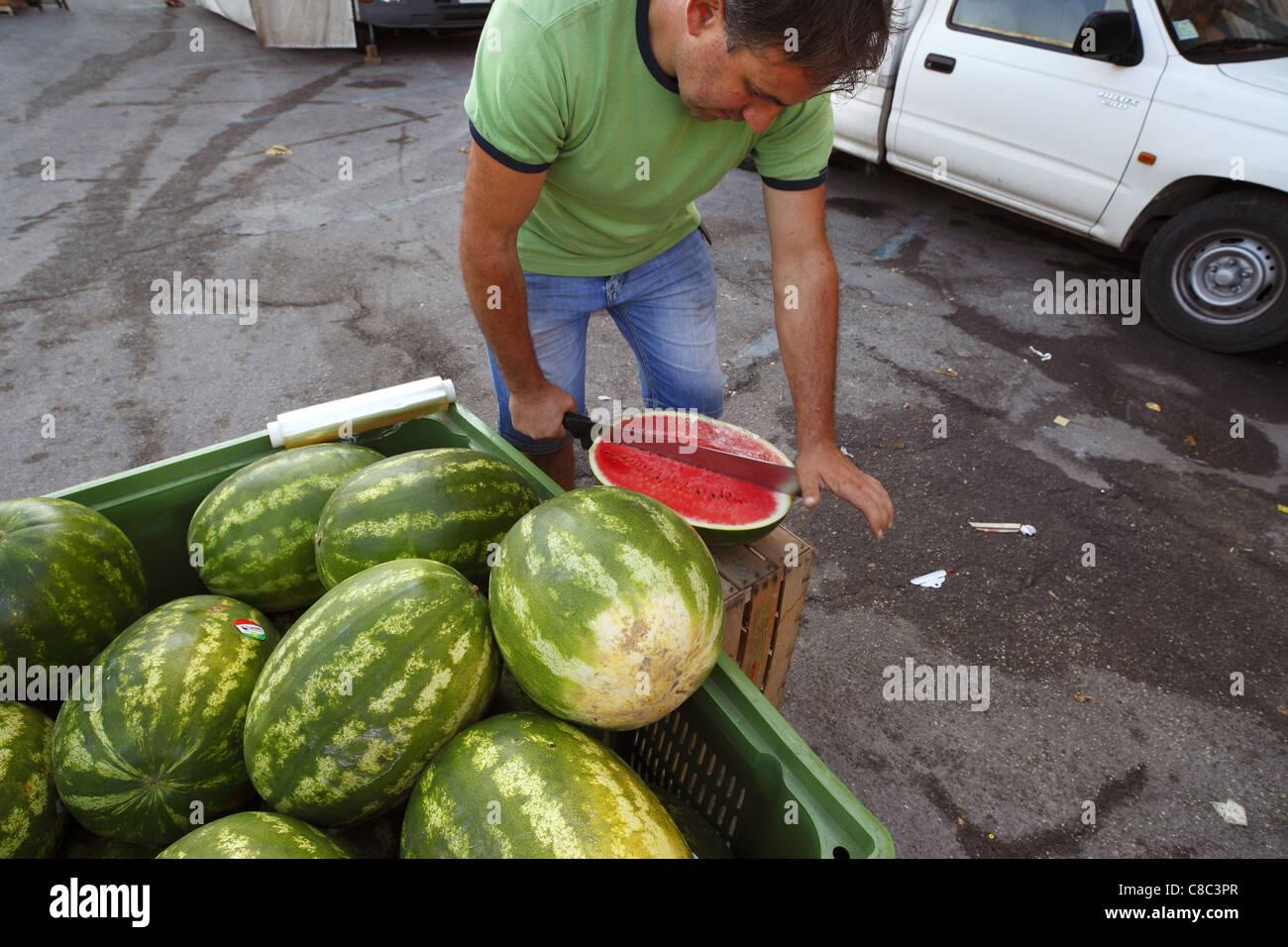 Un vendeur de fruits au melon d'eau prépare au marché de rue à Orvieto, Italie. Photo Stock