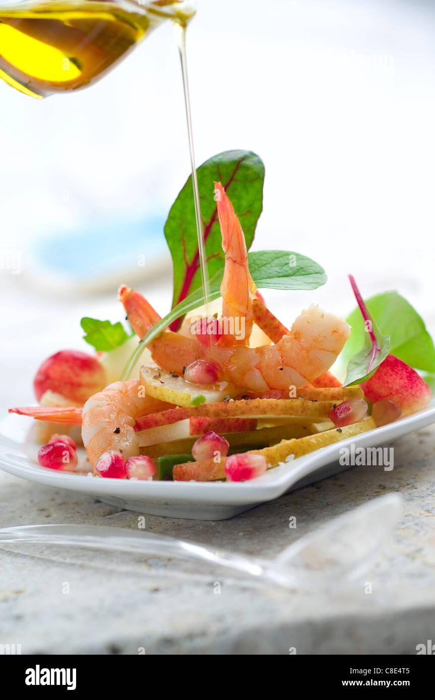 Verser une goutte d'huile d'olive sur la salade de crevettes et de poires Photo Stock