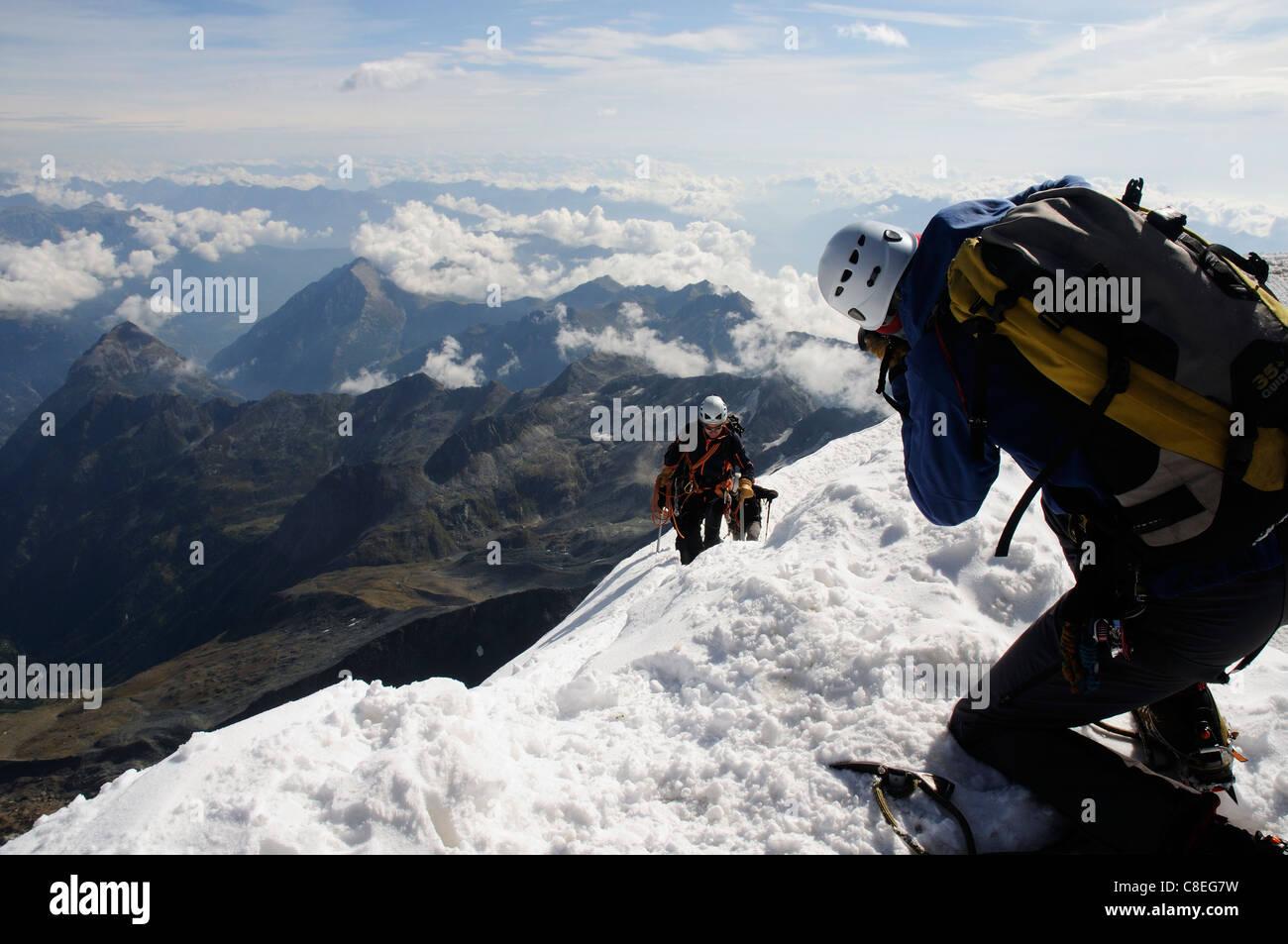 Un photographe à prendre des photos que d'une équipe de grimpeurs atteindre le sommet d'un pic Photo Stock