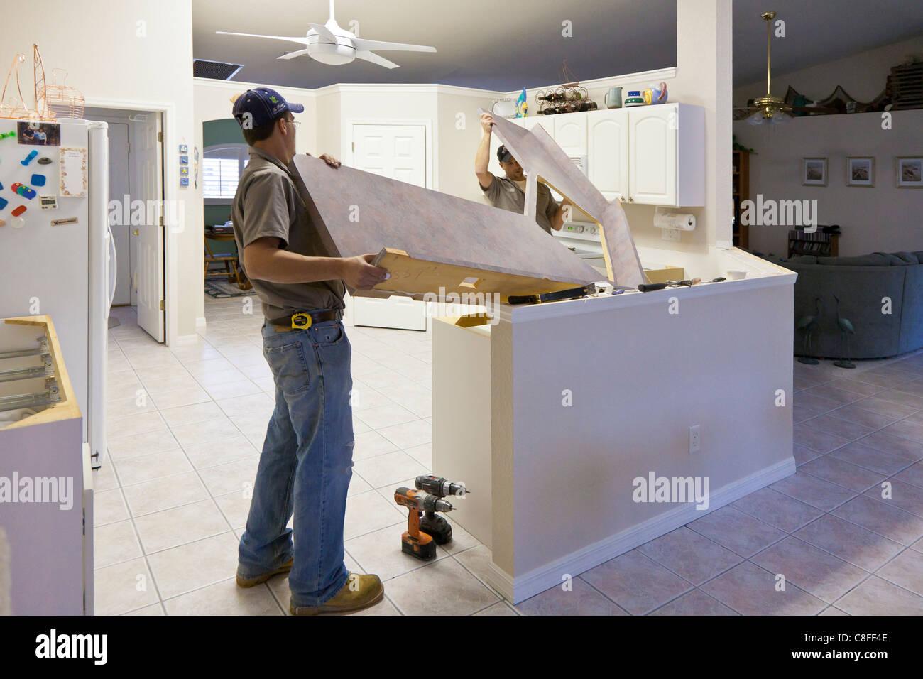 Deux hommes ascenseur comptoir Formica des armoires de cuisine moderne au cours d'un projet de rénovation Photo Stock
