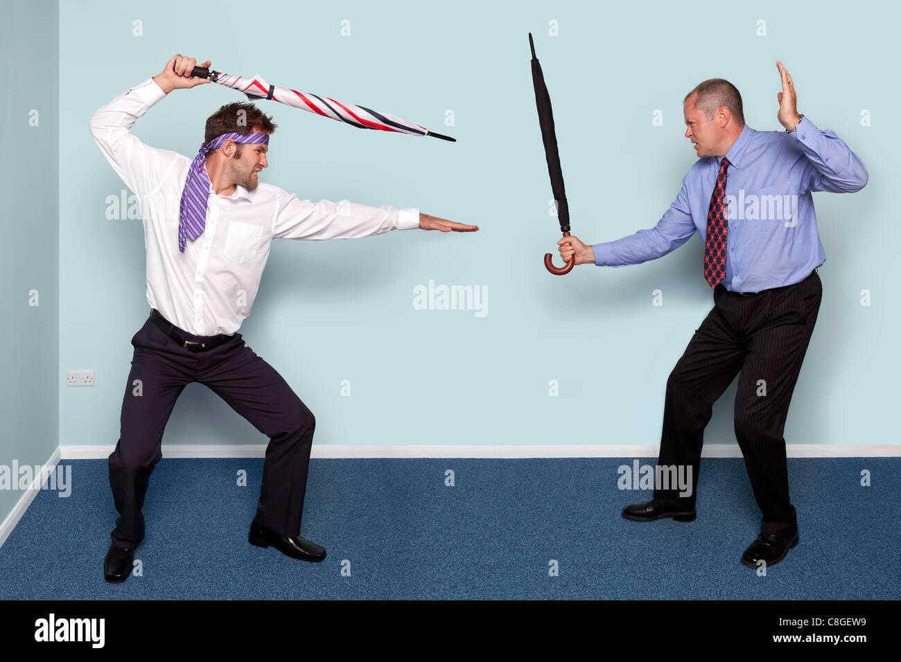 Photo de deux hommes d'avoir un combat à l'épée à l'aide de parapluies, bonne image Photo Stock