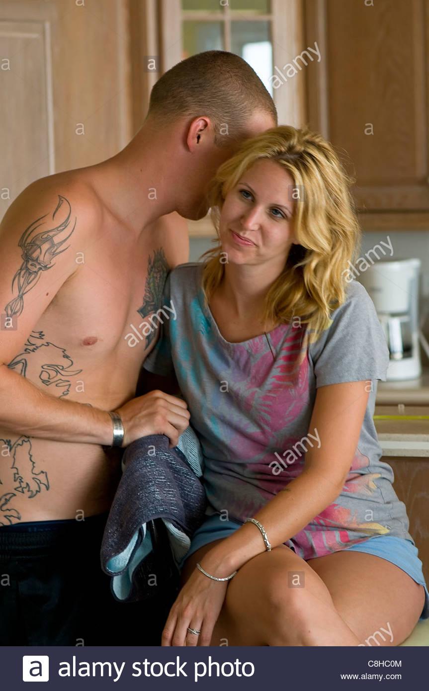 Un jeune couple matin après leur mariage chuchoter dans la cuisine. Photo Stock