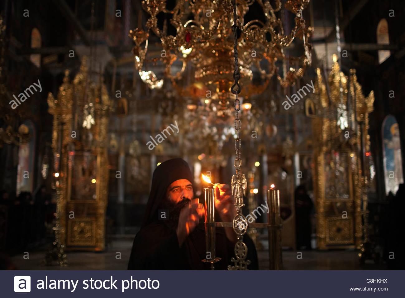 Un moine allume une bougie lors d'un service au monastère Xenofontos. Photo Stock