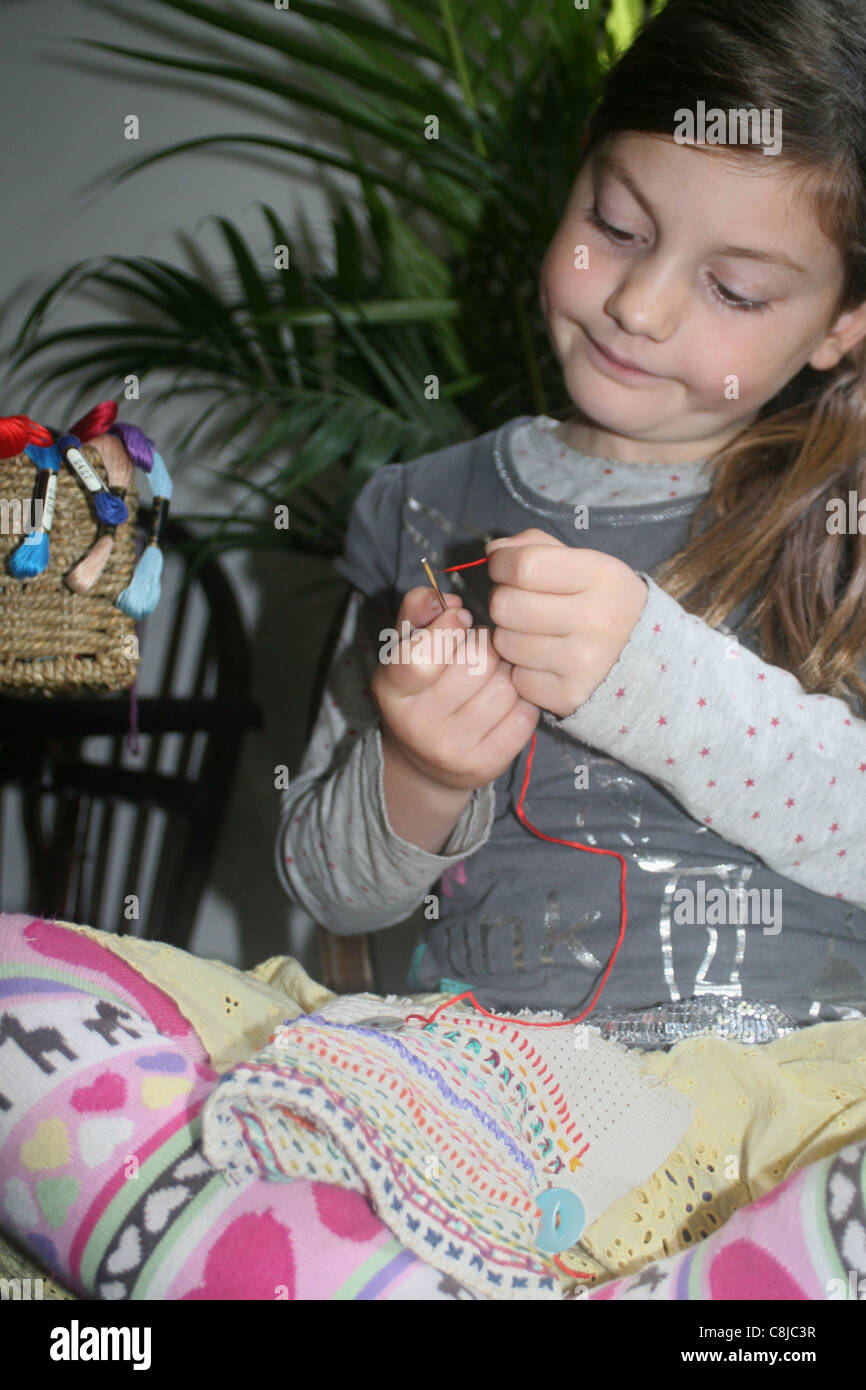 Jeune fille enfiler une aiguille à coudre aida bord , UK , Angleterre Photo Stock