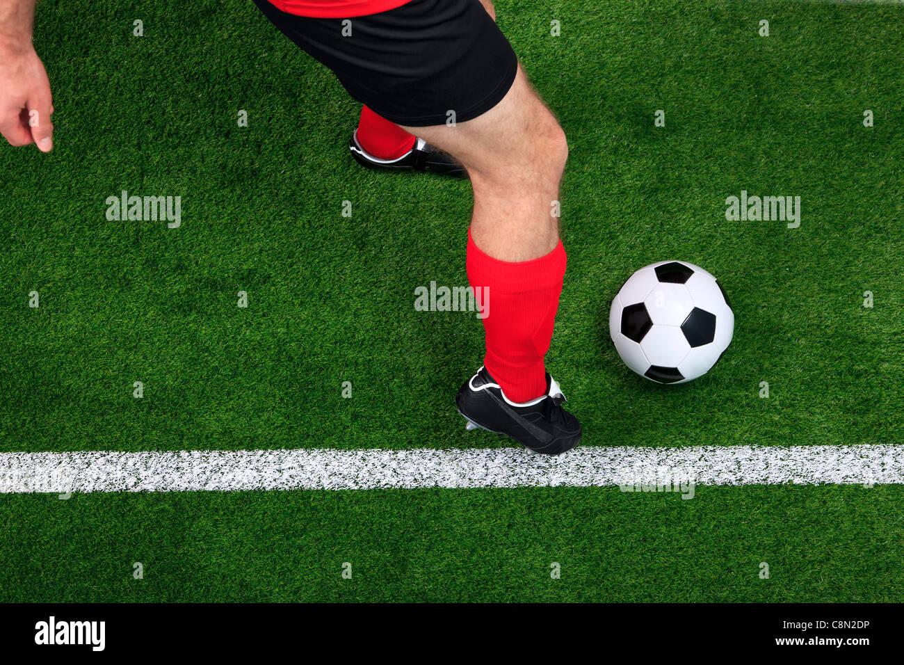 Photo prise à la verticale d'un joueur de soccer ou de football de dribbler avec le ballon sur la ligne Photo Stock