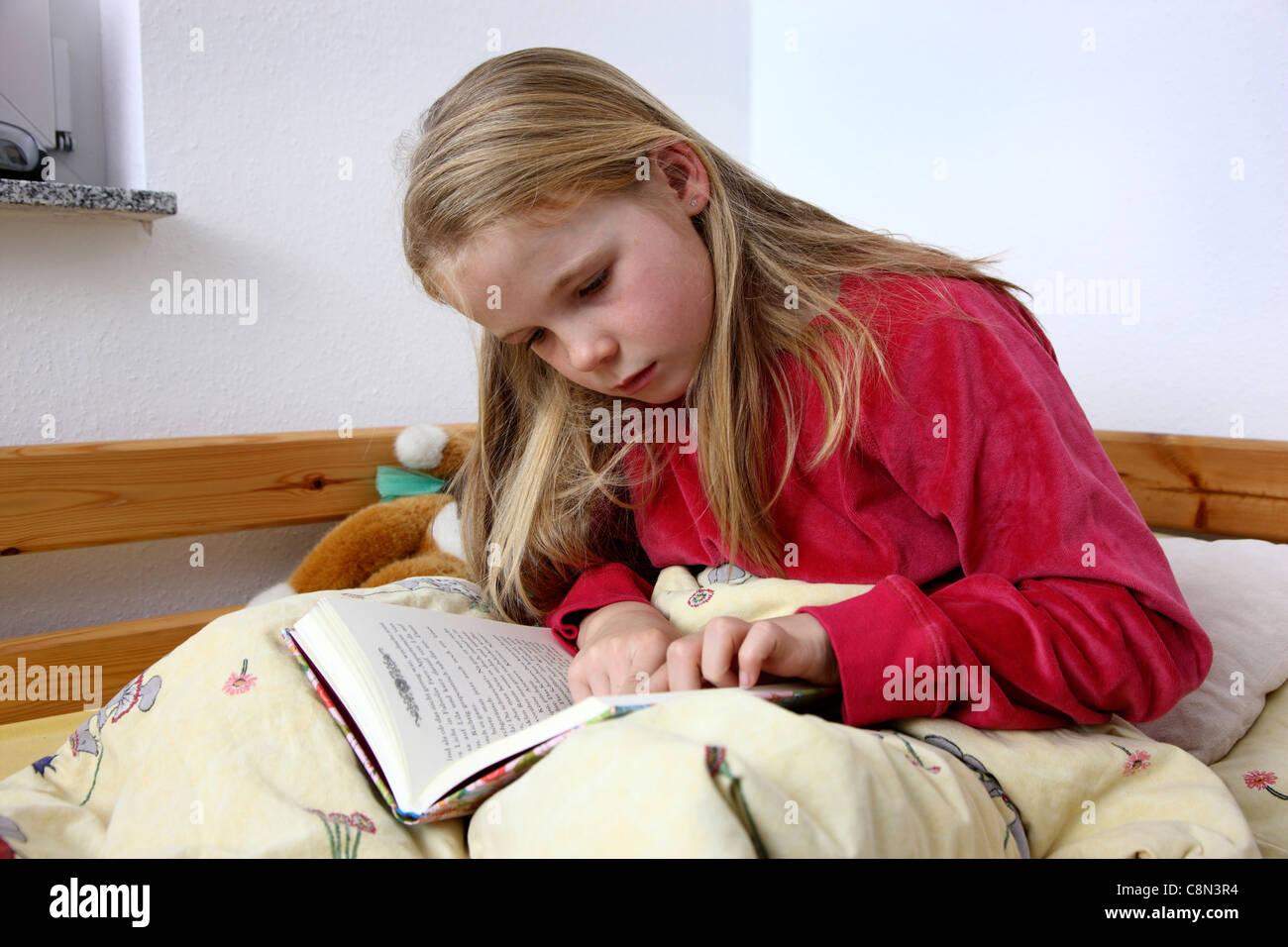 Jeune Fille 10 Ans Lire Un Livre Dans Son Lit Banque D