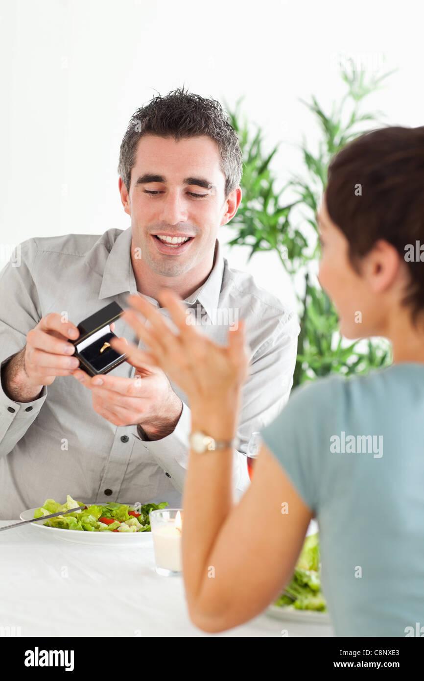 L'homme propose de sa charmante petite amie pendant le dîner Photo Stock