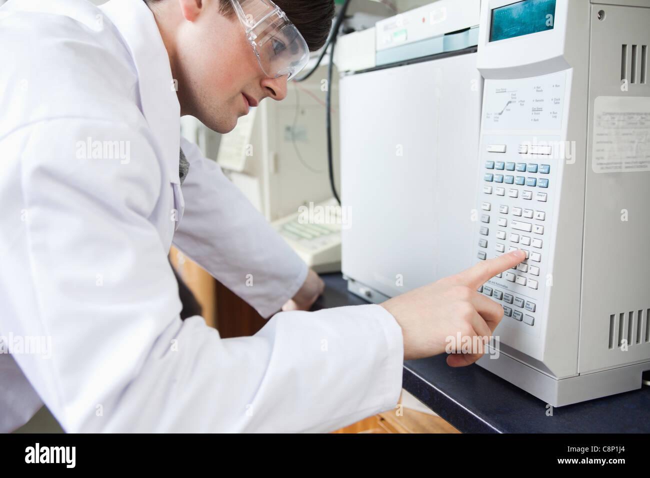 Étudiant en sciences à l'aide d'un four à chambre de laboratoire dans un laboratoire Photo Stock
