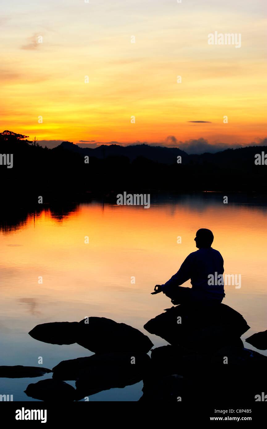 Lever du soleil silhouette d'un homme méditant sur des pierres sur un lac. L'Andhra Pradesh, Inde Photo Stock