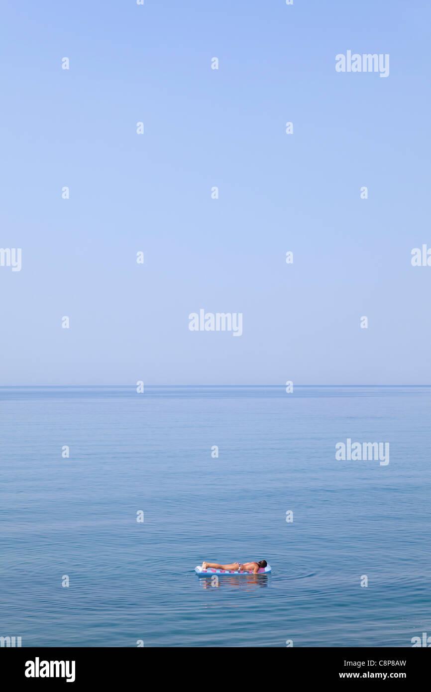 Flottant sur un matelas d'air dans la mer bleue Photo Stock