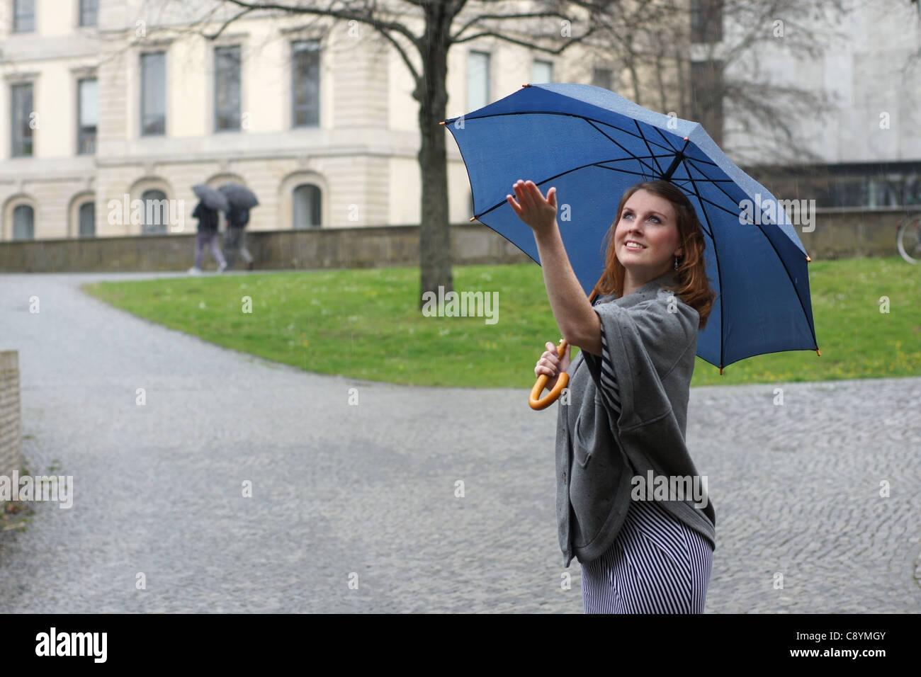 Jeune femme avec parapluie appréciant la pluie Banque D'Images
