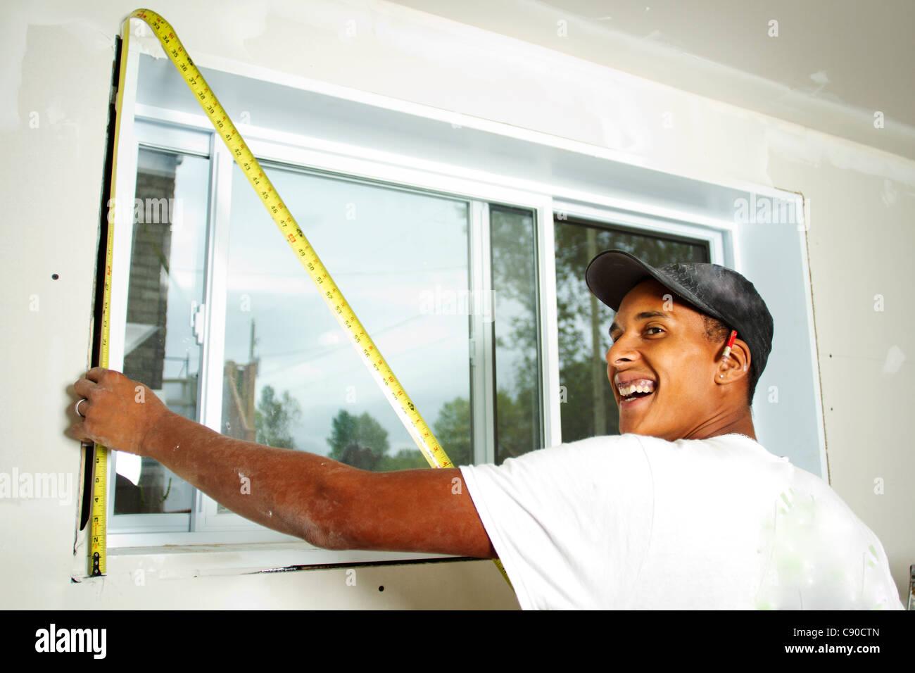 Travailleur ayant un ruban de mesure contre un mur à prendre les mesures Photo Stock