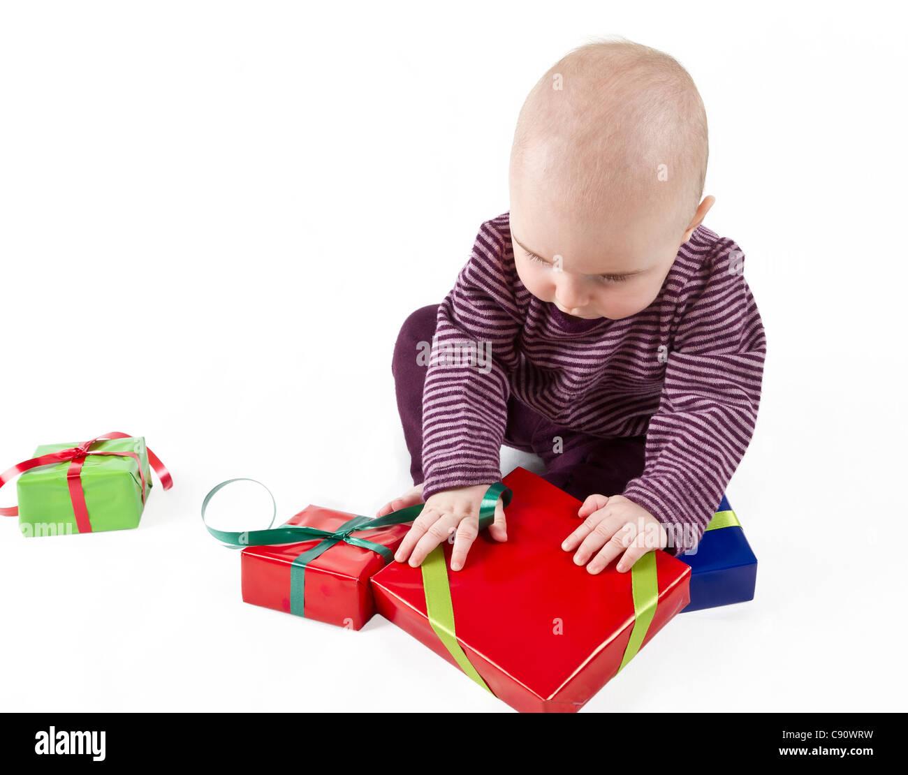 Déballage du jeune enfant présent rouge. fond blanc. Personne seule Photo Stock
