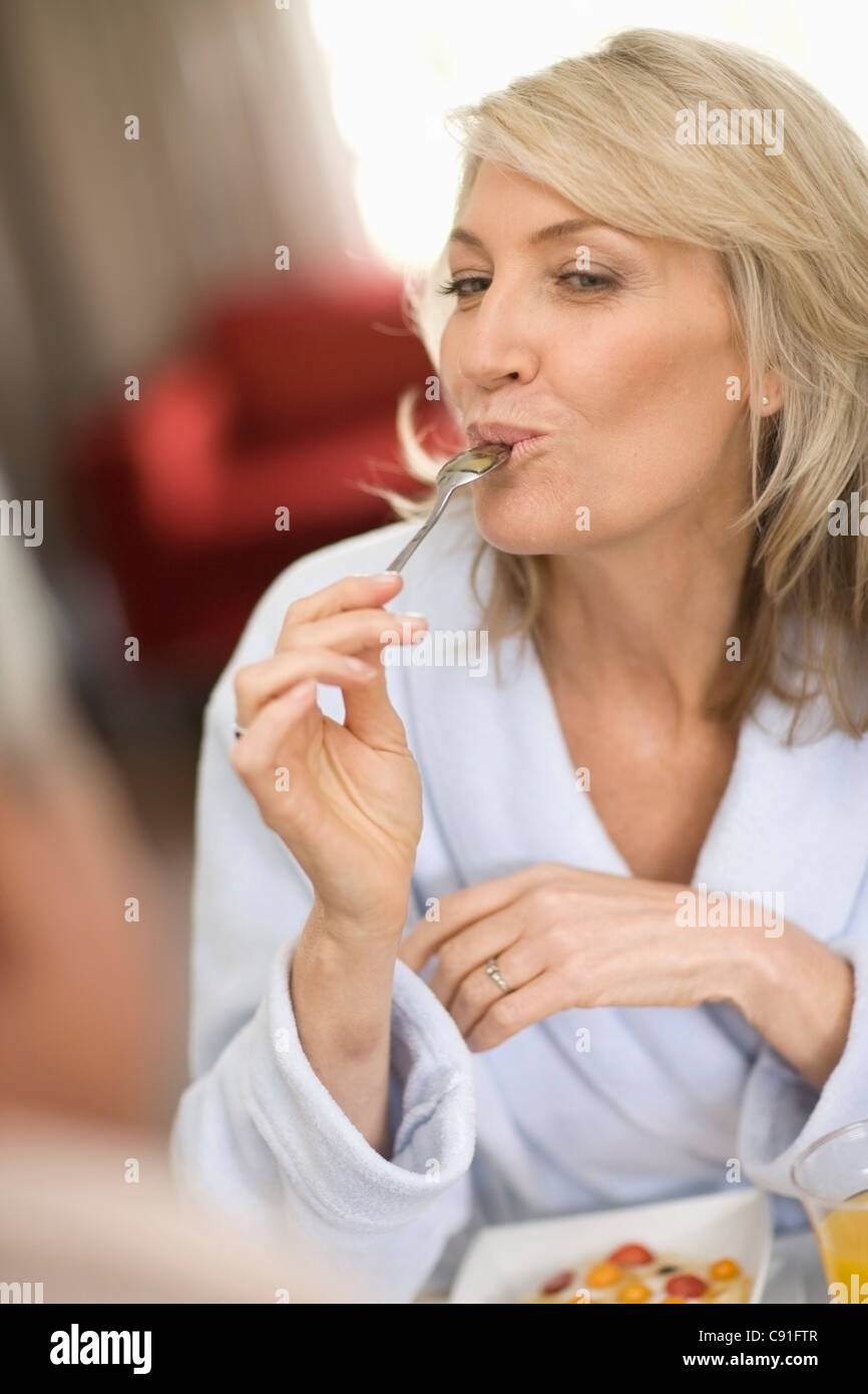 Smiling woman eating breakfast Photo Stock