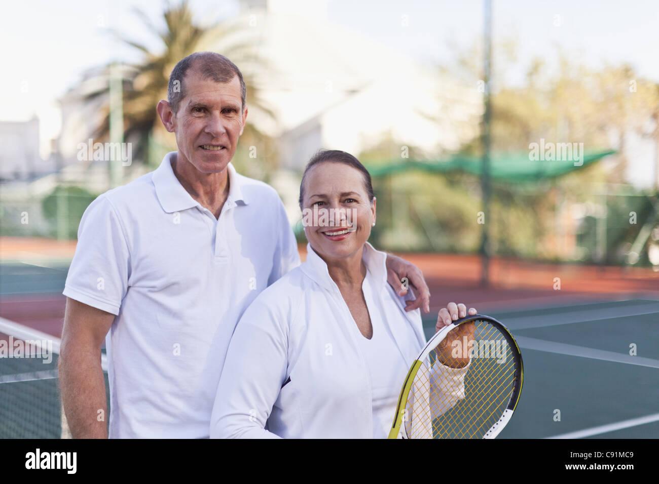 Vieux couple debout sur un court de tennis Photo Stock