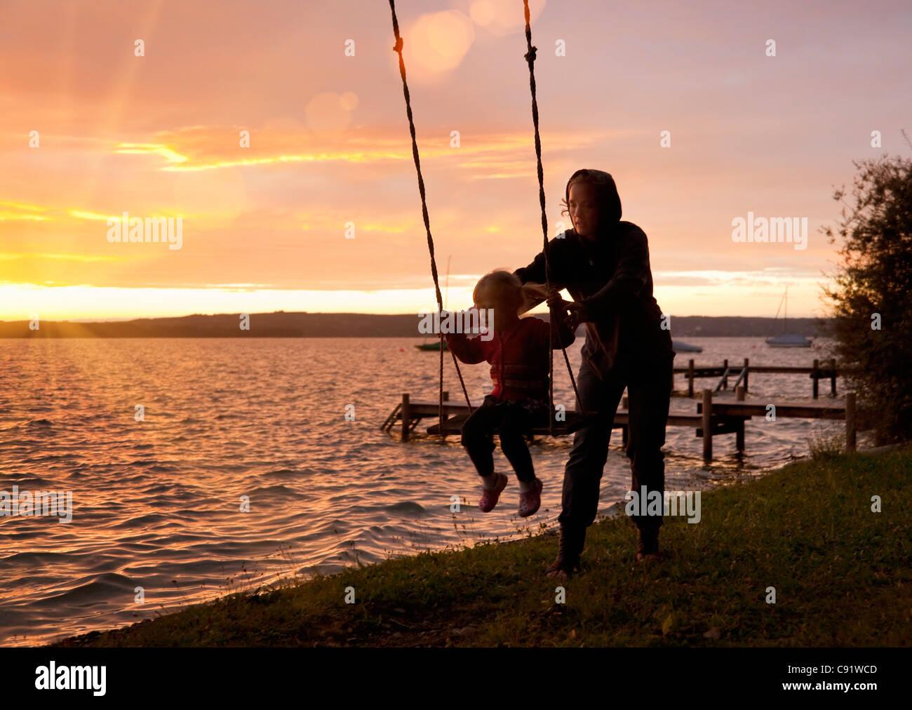Mère fille poussant on swing Banque D'Images