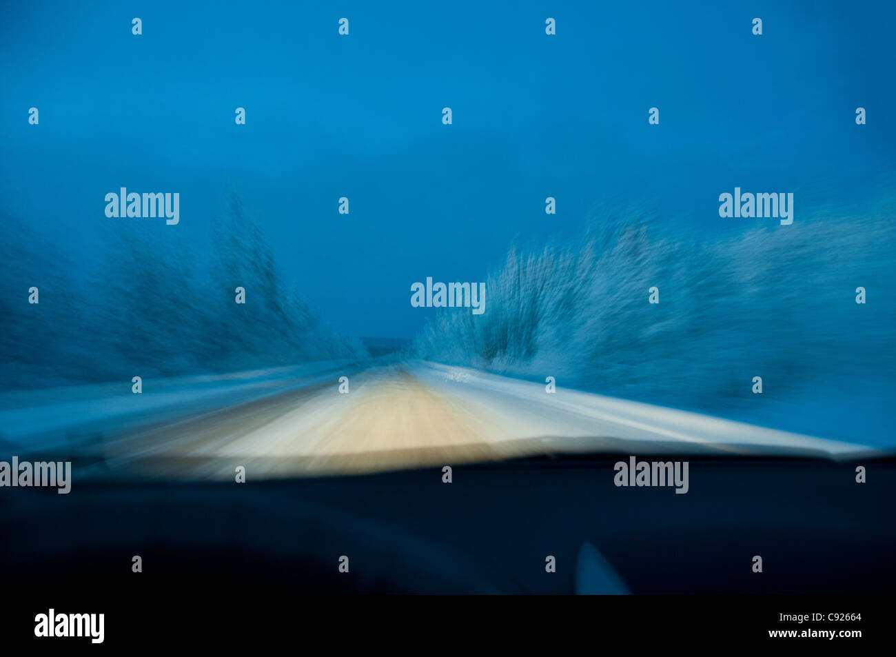 Point de vue du conducteur de la conduite dans la soirée sur une route en neige Parc national Kluane, Yukon Territory, Canada Banque D'Images